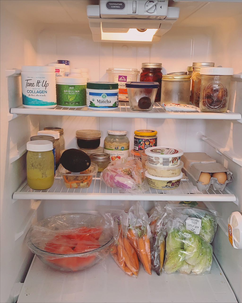 refrigerator with stocked foods from the grocery store like matcha, collagen, and fresh produce